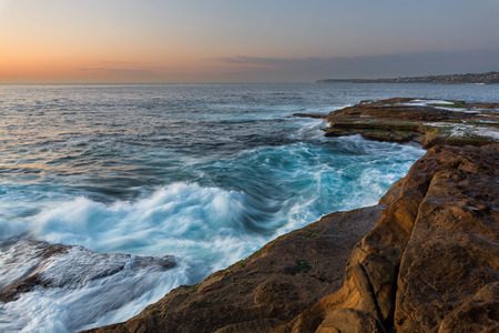 unrest: Sunrise seascape with unrest sea and blue water and with sky lit orange rocks Stock Photo