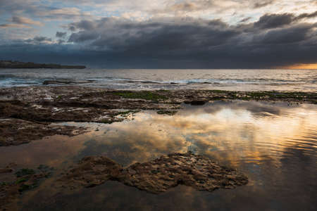 calm water: Seascape sunrise long exposure with calm water puddle and grim sky Stock Photo