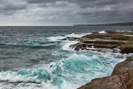 choppy: Stormy ocean in Sydney with gray heavy clouds and unsert sea with white foam and cyan color