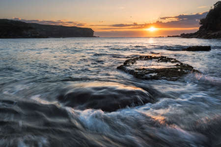 rushing water: Sunrise seascape with rushing water and rising sun and backlit waves