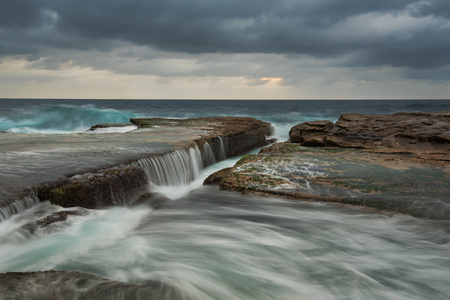 falling tide: Cold stormy seascape with rushing wave and flowing water Stock Photo