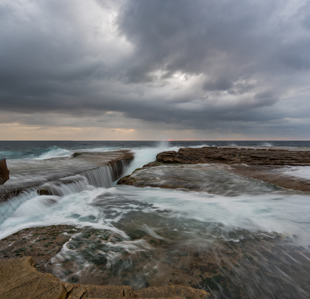 falling tide: Cold stormy panoramic seascape with rushing wave and flowing water Stock Photo