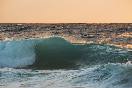 crooked: A single cyan crooked wave on surise bathing in warm orange or peach light Stock Photo