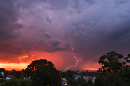 lightnings: Thunderstorm with lightnings hitting the city during sunset with lots of color