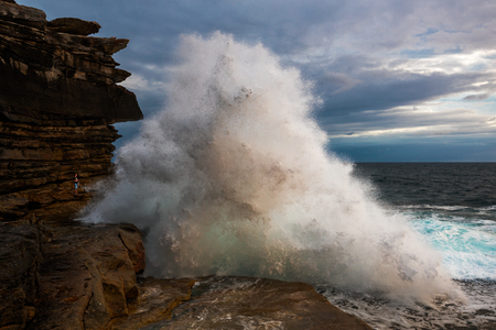 Brave man standing at the edge facing huge wave coming at him. Stock Photo