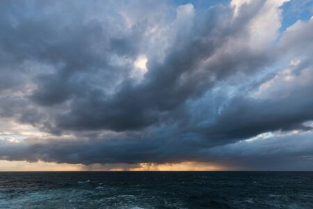 approaching: Approaching storm cloud with rain over the sea during sunrise