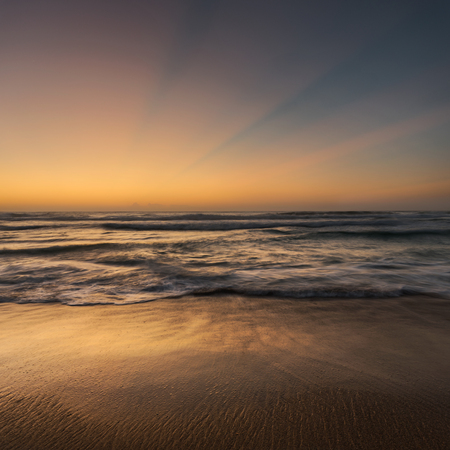 soft diffused light: Golden hour seascape with soft light, god rays and golden sand Stock Photo