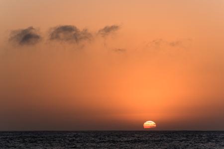 sol naciente: Sol naciente parcialmente ocultas con las nubes de detrás del mar Foto de archivo