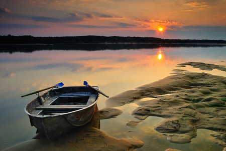 mirror on the water: Sunrise on the river with a sand moored boat and calm mirror water surface