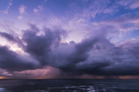 incoming: Approaching storm cloud with rain over the sea during sunrise