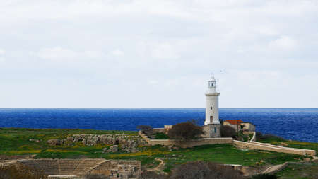 teatro antiguo: Old white lighthouse and ancient theatre ruins near the deep blue sea