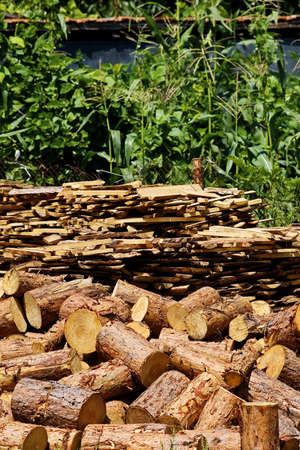 stored: Lumber for heating stoves stored in the greeny farm yard in Eastern Europe, where firewood is a common source of energy during the wintertime