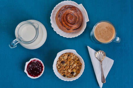 Light healthy breakfast consists of cereals muesli, cinnamon bun, latte milk and jam on aquamarin background suitable hotels or restauraunts