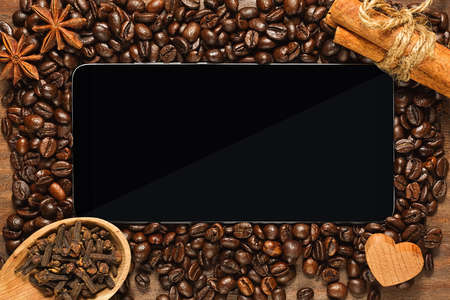 Smartphone or small tablet in top view framed by roasted coffee beans and condiments - cinnamon, clove seeds and anise