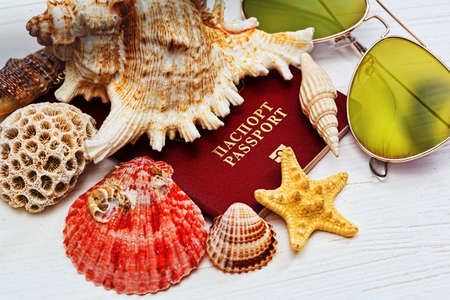 Russian passport covered by sea shells and starfish and sunglasses on the wooden desk