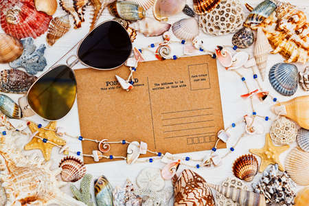 oldened: Vintage style blank postcard, sunglasses and necklace with a frame of sea shells - top view in mediterranean style
