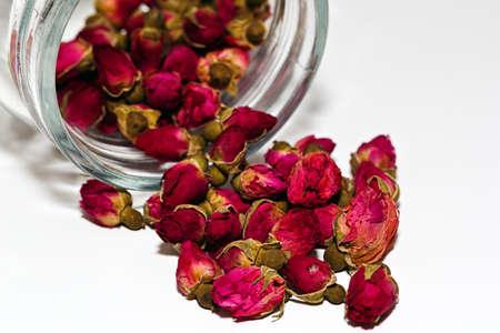material de vidrio: Some herbal rose tea in a glass jar on white background Foto de archivo