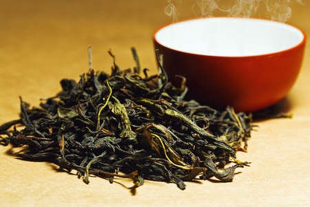 Pile of tea leaves near little cup in chinese traditional style Stock Photo