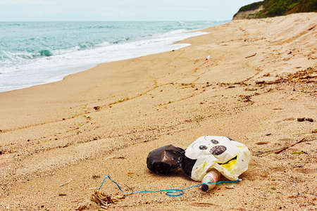 Old chilfrens balloon, plastic bottles and bags and oher garbage left on sand beach