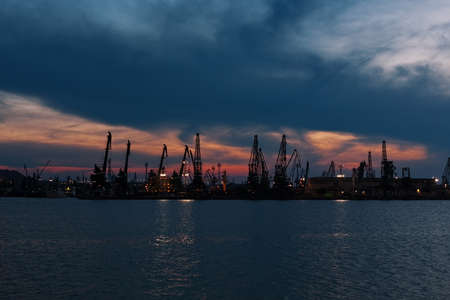 Trade harbor with port cranes in the sunset