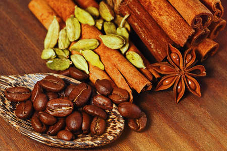 Roasted coffee beans in wooden spoon and different spices - cinnamon, cardamon, anise on the wooden table Stock Photo