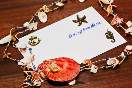 coulomb: Vacations and holiday concept. Post card with sea shells and star fish on wooden table.