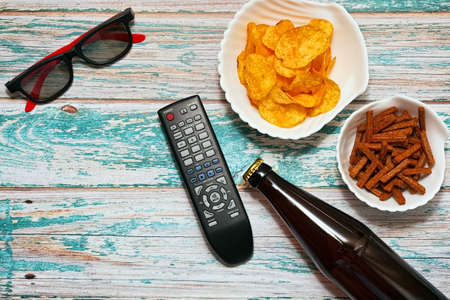 Home cinema party - beer bottle with different snacks, TV remote and glasses in horizontal top view