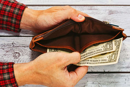 Man in checkered work shirt holding old leather wallet with just two US dollars - paying debt or poverty concept Stock Photo