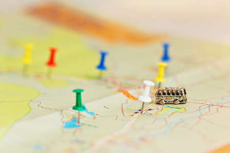 map pin: Map with colored pins and tiny bus on the road. Close-up capture with soft focus and accented depth of field.