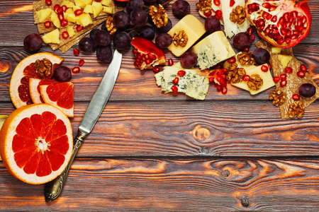 Healthy dieting meal in european style. Variety of refined cheese from different countries with fresh fruits such as grapes and garnet, walnuts and rye crackers. Nutritious lunch or wine appetizer.
