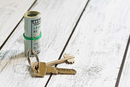 Renting or purchasing accommodation for US dollars currency- stack of one hundred bucks notes and a door lock key. Real estate deal for cash. Close-up capture, selective focus.