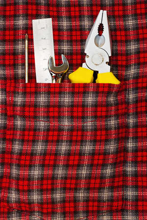 Hand repair tools in front pocket of checered work shirt - part of classic worker or mechanic outfit. Vertical close-up capture. Stock Photo