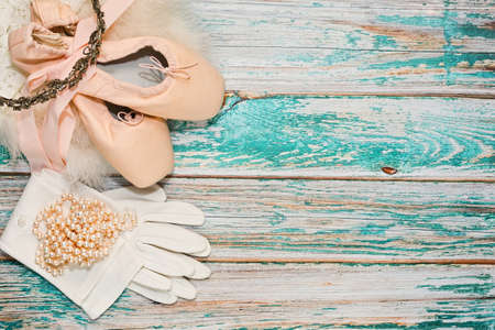 Ready to show ballerina accessories and props - pair of traditional ballet shoes, skirt with fur rim, gloves, pearl necklace and crown. Everything prepared for perfomance evening in theater. Top view. Stock Photo