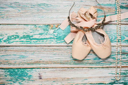 stage props: Classic ballet shoes with ribbons lie on wooden surface - theater stage - and some ballet show props - diadem with rhinestones and pearl necklace. Ballet practice or training concept. Top view.