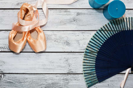 Silk ballet shoes calling pointes lie on wooden rough surface - theater stage. Blue hand fan and candles nearby usable like props in theater perfomance. Behind the ballet scenes concept.