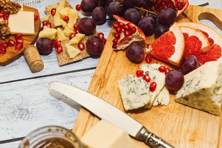 Perfect appetizer and wine snack - few varieties of cheese with different fresh fruits sliced on cutting board on wooden background. Close-up capture, selective focus.