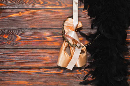 Pair of new ballet dancing shoes with hard insoles hand nearby black feather boa on the wooden background. Ready to dancing show concept. Place for text.