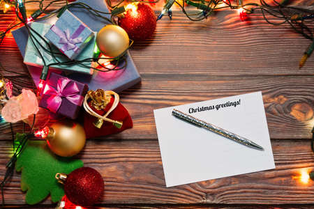 Pile of Christmas gift boxes, New Year decorations, toys and colorful garland and a post card with greetings tagline and place for text on wooden table. Top view, selective soft focus.