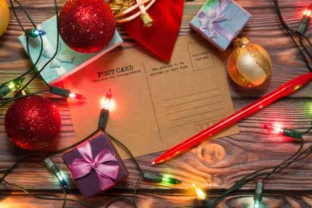 Vintage style post card surrounded by Christmas gift boxes, New Year decorations and colored garland. Winter holidays greetings and congratulations concept. Top view, soft focus.
