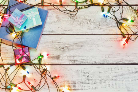 Christmas presents in tiny gift boxes collected on the rough painted wooden table in retro style and traditional New Year colorful garland. Winter holidays concept. Top view, place for text.
