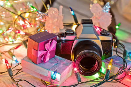 New Year or Christmas presents on the wooden table - pile of tiny gift boxes and a vintage style camera lit by traditional garland and ready to celebration ceremonies. Selective focus.