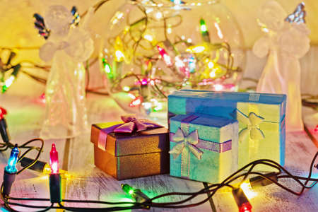 Pile of gift boxes ready to New Year and Christmas celebrations illuminated by colorful garland and two angel figurines. Traditional winter holidays concept. Close-up capture, selective focus. Standard-Bild