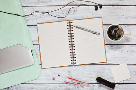 Working place in loft style on wooden desk of student or freelancer - laptop in case, opened blank sketch pad and office accessories and a cup of coffee stands nearby. Top view, flat lay.