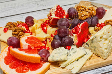 Perfect gourmet snack in european cuisine style - sliced refined aged cheese mixed with fresh fruits and nuts on wooden board, ready to eat wine appetizer. Close-up capture, selective focus.