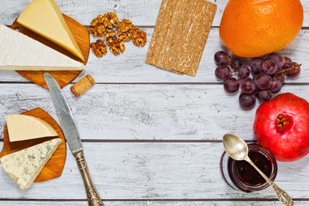 Refined appetizer or wine snack - few varieries of gourmet european cheese collected with rye crackers, walnuts and fresh fruits and served on wooden retro style table. Top view, place for text. Standard-Bild