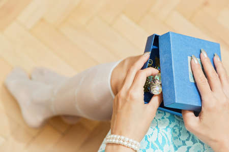 Young female person dressed  in blue unpacking a gift box with a Christmas, New Year or Valentine present - something shiny and brilliant. First person high angle view, selective focus.