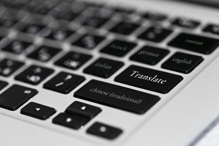 PC keyboard with different foreign languages names on keys - multilingual translation online service working with plenty varieties of languages. Close-up capture, selective focus.