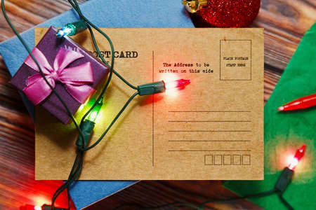 Christmas or New Year congratulation post card writing concept. Vintage card with traditional winter holidays symbols - gift boxes, tree decorations and garland lights. Top view, place for text.