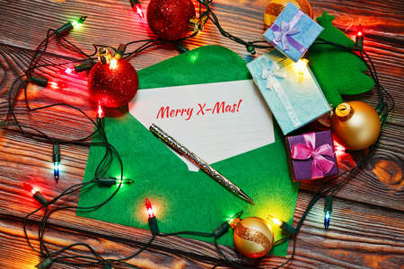 Opened green crafted envelope with a postcard with X-Mas congratulations surrounded by traditional New Year and Christmas decorations and symbols - tree toys, garland and gift boxes.