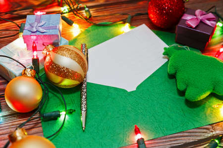 Opened holiday envelope with a post card prepared for New Year congratulations. Christmas tree decorations, toys, gift boxes and shiny garland. Close-up capture, selective focus. Standard-Bild
